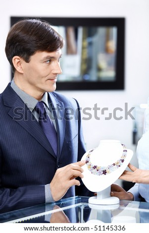 The man of average years in shop chooses a necklace - stock photo
