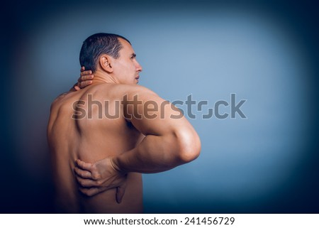 the man of European appearance brunet holding hands behind his back feels pain in the back cross process - stock photo