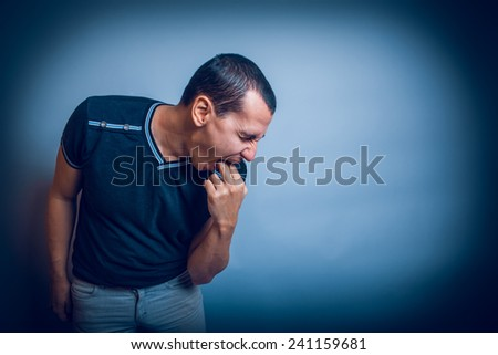the man of European appearance brunet sick causes vomiting putting two fingers in his mouth on a gray background cross process - stock photo