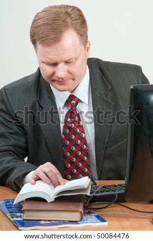 The man of forty five years in a grey suit and a red tie works on the computer.