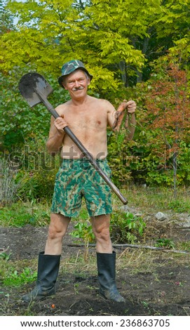 The man on garden with spade and carrots in his hands. - stock photo