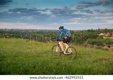 the man on the bike in the grass on the  sky and trees background