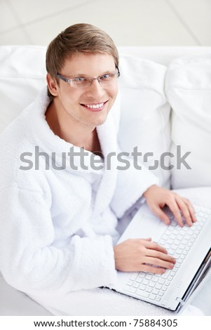 The man on the couch with a laptop - stock photo