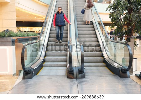 The man on the escalator at the mall - stock photo