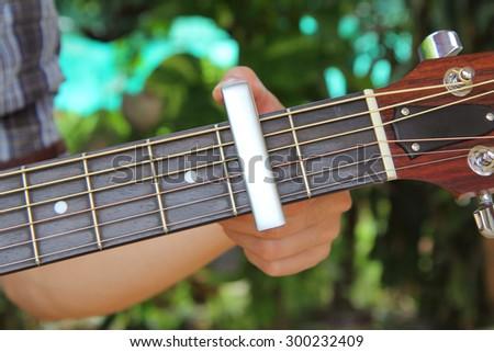 the man pin capo to the guitar - stock photo