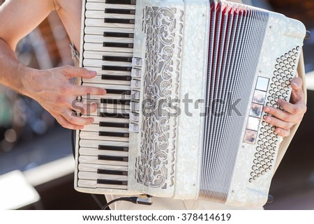 The man playing an accordion. Accordion closeup. - stock photo