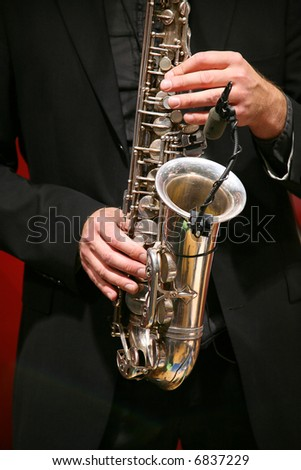The man plays on a saxophone