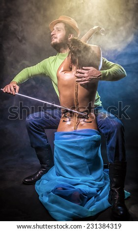 The man plays on the woman as on a violin - stock photo