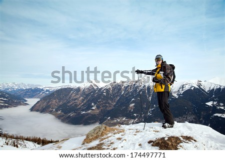 The man points on mist over valley, Austrian Alps