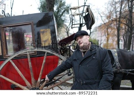 The man posing on the brougham background in autumn, Russia - stock photo