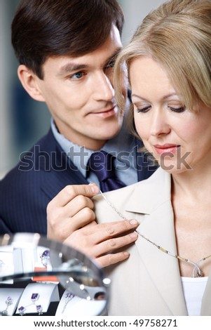 The man puts on to the woman a jeweller necklace - stock photo