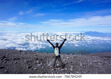 The man raised his hand on semeru mountain peak