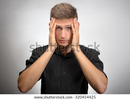 The man really tired, he holds his head with his hands. Gray background - stock photo
