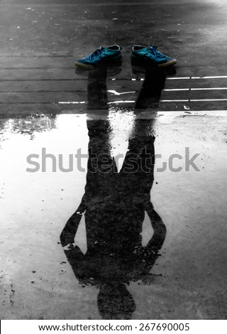The man reflection in the water after raining - stock photo