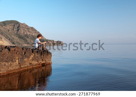 The man resting on the rock, sunset, sea. - stock photo