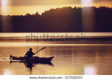 The man rowing oars in boat of kayak type on the lake at early evening. Golden sunset.Summer time, active recreation. Healthy lifestyle and care about mental health, resting in  privacy and peace.