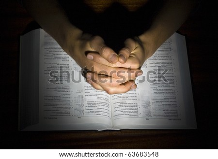 The man's combined hands praying on the bible isolated in a black background