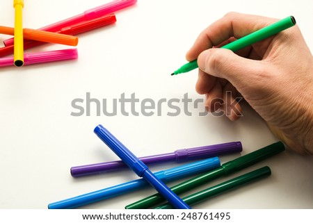 the man's hand, ready to draw a picture felt-tip pen - stock photo