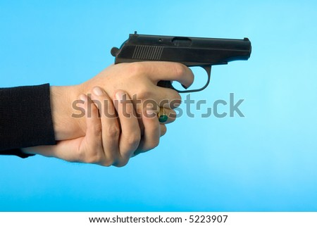 the man's hand with gun isolated on blue