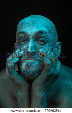 The man's head is covered with frost. His terrible eyes. Close-up portrait. - stock photo
