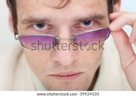 The man seriously and strictly looks at us over glasses - stock photo