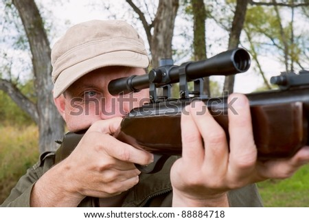 The man Shooting from a gun. Training shooting from an air rifle in the autumn afternoon - stock photo