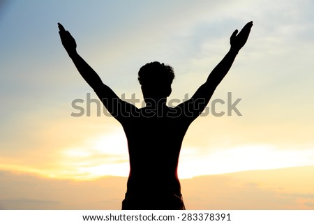 The man silhouette alone at sunset in desert with outstretched arms