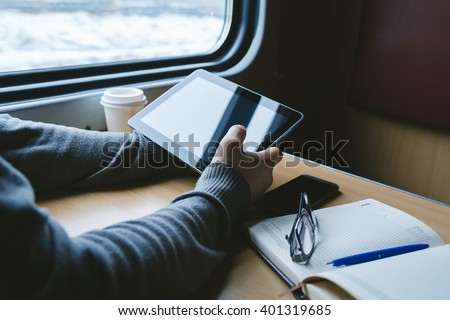 The man sits at a table in a train with a tablet in hands - stock photo