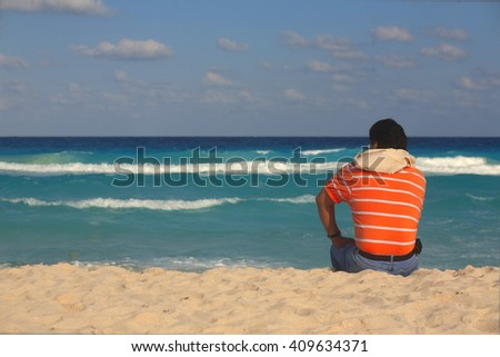 the man sitting on the sand by the sea