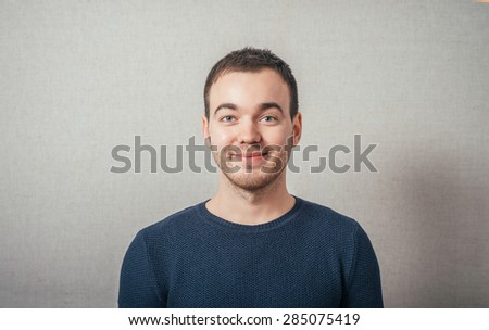 The man  smiling. On a gray background. - stock photo