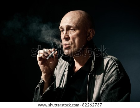 The man smokes a cigaret against a dark background - stock photo