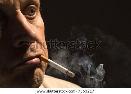 The man smokes a cigarette close up - stock photo