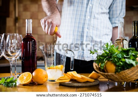 The man squeezes orange juice in a decanter for the preparation of sangria for home party, home kitchen interior. Homemade food and drinks - stock photo