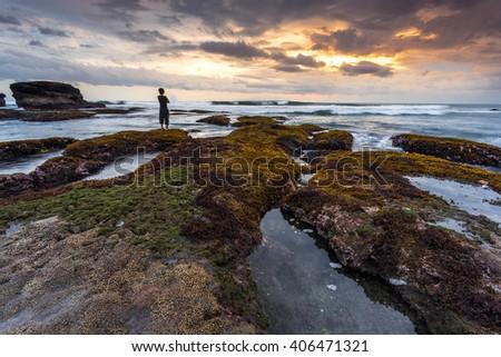 The man standing alone during sunset at Melasti Beach, Bali Indonesia - stock photo
