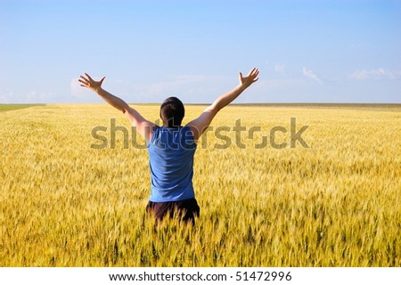 The man stands a back in an autumn field. Has lifted hands upwards - stock photo