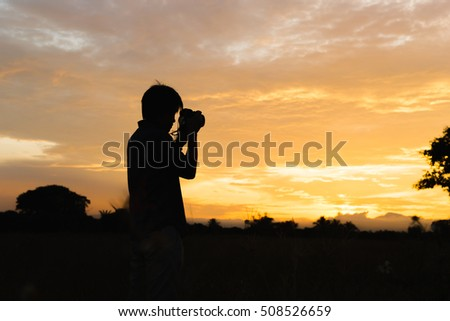 the man take a picture at field in the evening.