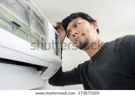 the man trying to fix air condition by himself