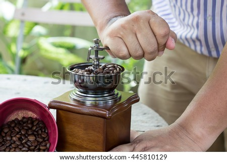 The man use old vintage coffee grinder with coffee beans - stock photo