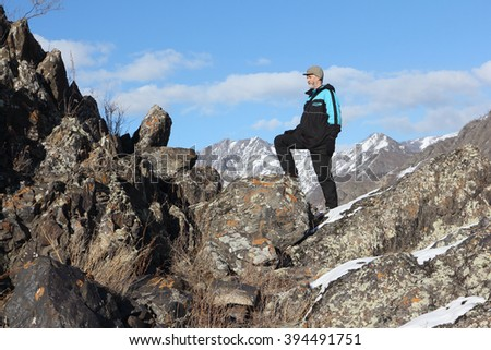 The man with a beard in a black jacket going by the rock in the mountain district, Altai, Russia