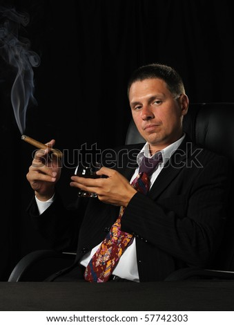 The man with a cigar and a glass of cognac. A dark background