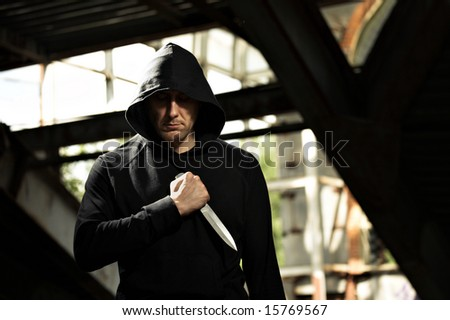 The man with a knife in black in not completed building