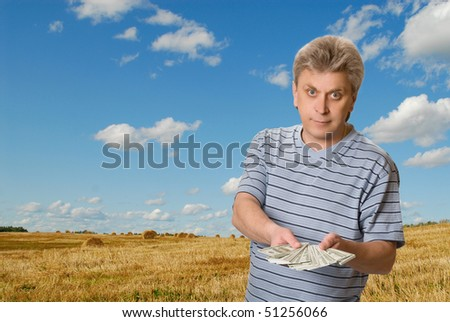 The man with a pack of money on background landscape - stock photo