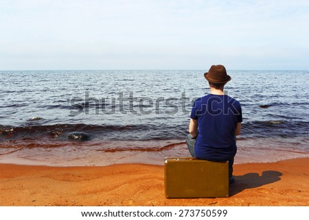 The man with a suitcase on a beach - stock photo