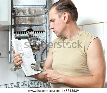 The man with a wrench looks the instruction on repair a gas water heater.  - stock photo