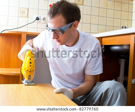 The man with an electro fret saw - stock photo