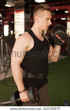 The man with dumbbells in sports club work hard.