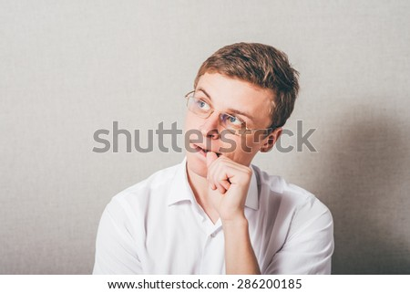 The man with glasses bites his nails. On a gray background. - stock photo