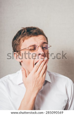 The man with glasses tired sleepy, yawning. On a gray background. - stock photo