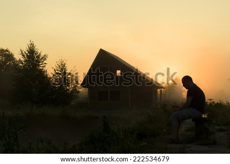 the man with phone early in the morning stays at home on the bank of a pond at the - stock photo
