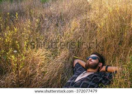 the man with the glasses has a rest lying on a meadow in the warm light of sunset - stock photo